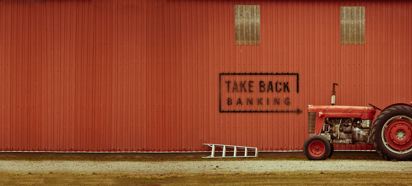 Take back banking painted on a barn with a tractor