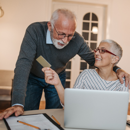 Mature man and woman using debit/credit card at laptop